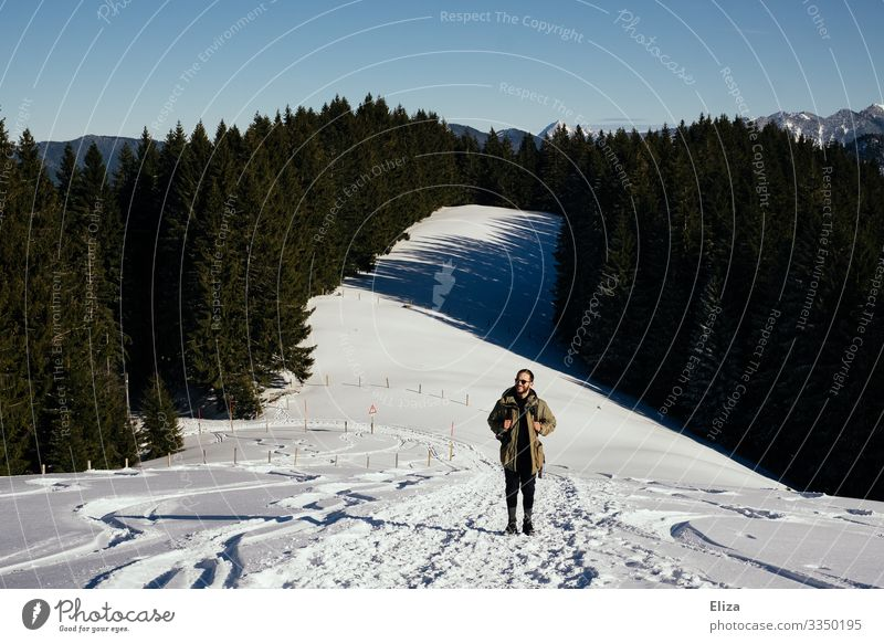 A man hiking in the mountains in winter with lots of snow Winter Hiking Snowscape Man slope Blue sky sunshine Mountain Nature Trip Bavaria Beautiful weather