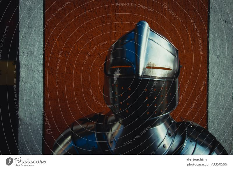 lifted off / not with the armor. A shining knight's armor with helmet. to be seen only up to the shoulder area, before a red wall. Joy Harmonious Trip