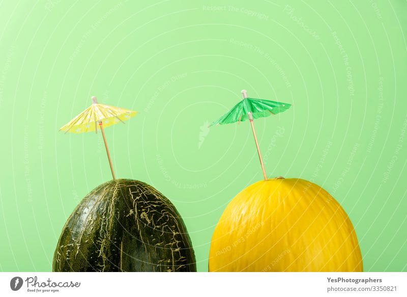 Two melons with cocktail umbrella, Summer melon drink concept Fruit Dessert Organic produce Delicious colorful Conceptual design cucurbitaceae diet food