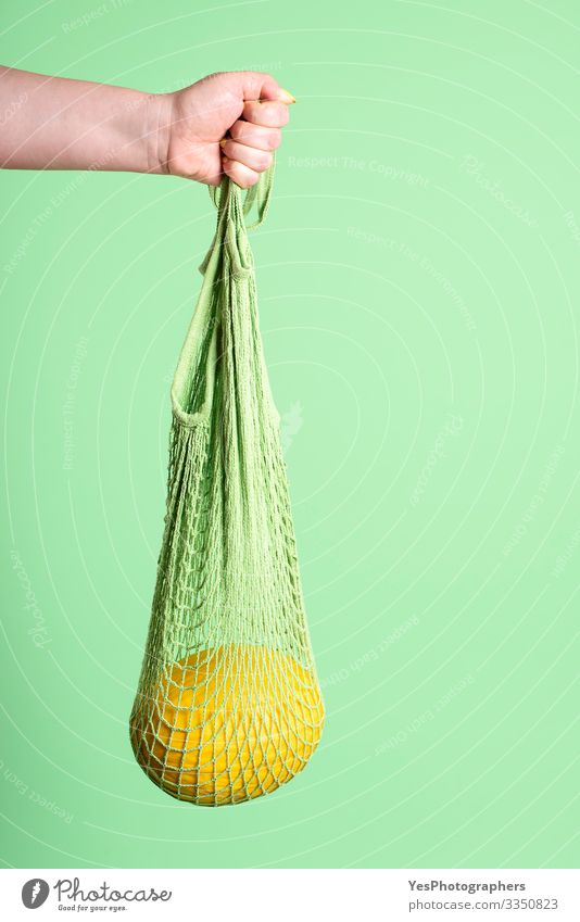 Yellow melon hanging in reusable mesh shopping bag Fruit Dessert Organic produce Diet Shopping Healthy Eating Feminine Hand Green buying fruits colorful