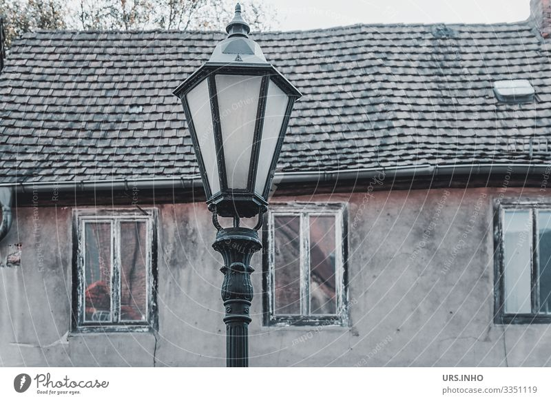 Streetlight in front of an old house Village Deserted Building Wall (barrier) Wall (building) Facade Window Roof Old Poverty Hideous Retro Brown Gray Black