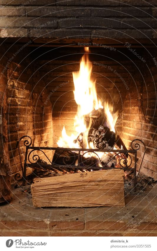 fire burning in old fireplace with charred bricks Winter Metal Brick Old Dirty Black wood Flame heat hearth ashes Rustic Second-hand Weathered Glow Spark Cozy