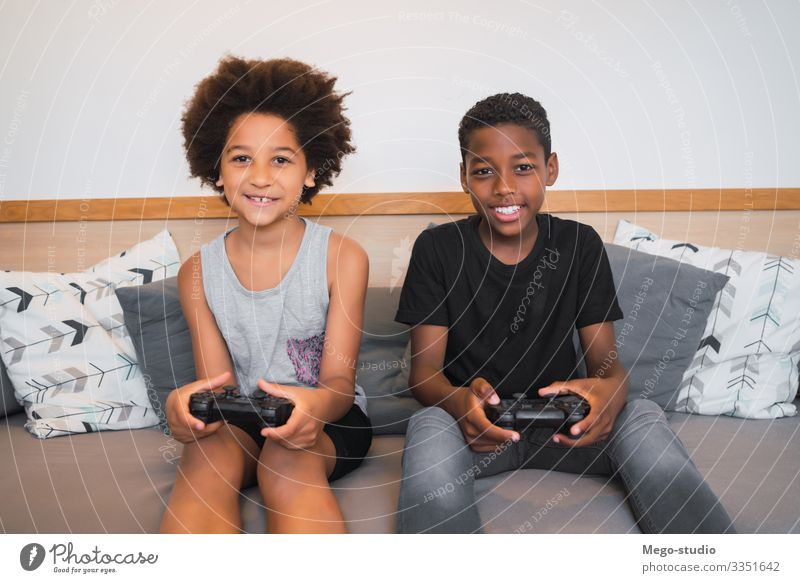 Two brothers playing video games at home. Lifestyle Joy Happy Leisure and hobbies Playing Sofa Entertainment Child Technology Human being Boy (child)