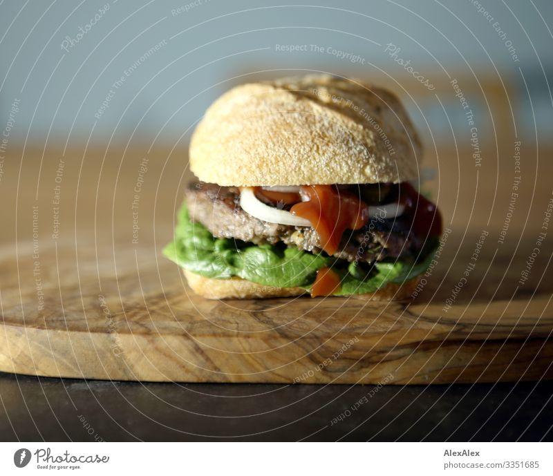 Hamburger sandwich with bread roll Food Meat Lettuce Salad Dough Baked goods Roll Sandwich Onion Minced meat beef Wooden board Chopping board Salad leaf Lunch
