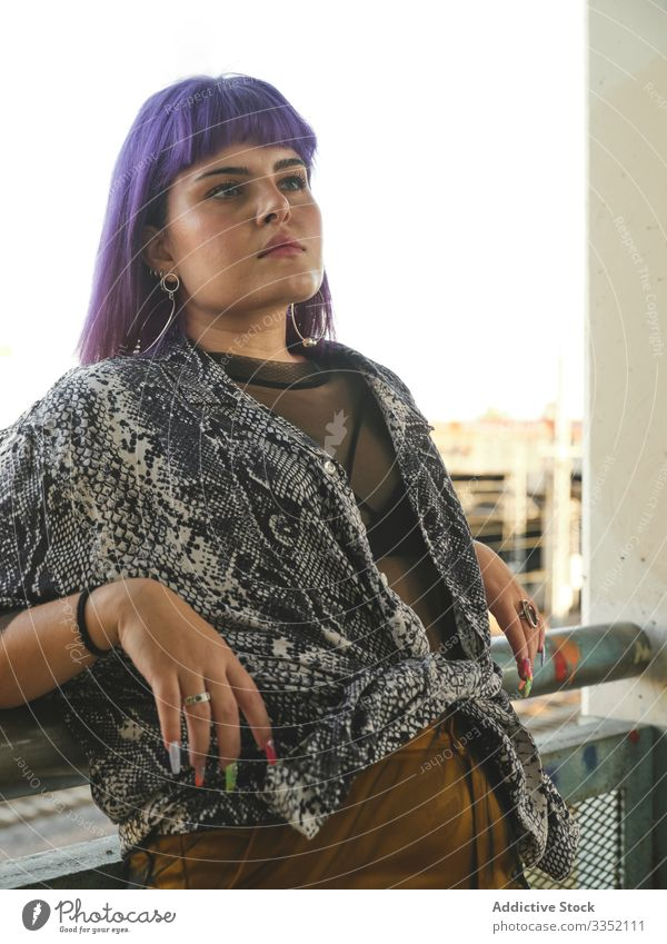 Woman with purple hair leaning on metal fence and looking away woman stylish urban hairstyle construction shiny structure district confident fashion young model