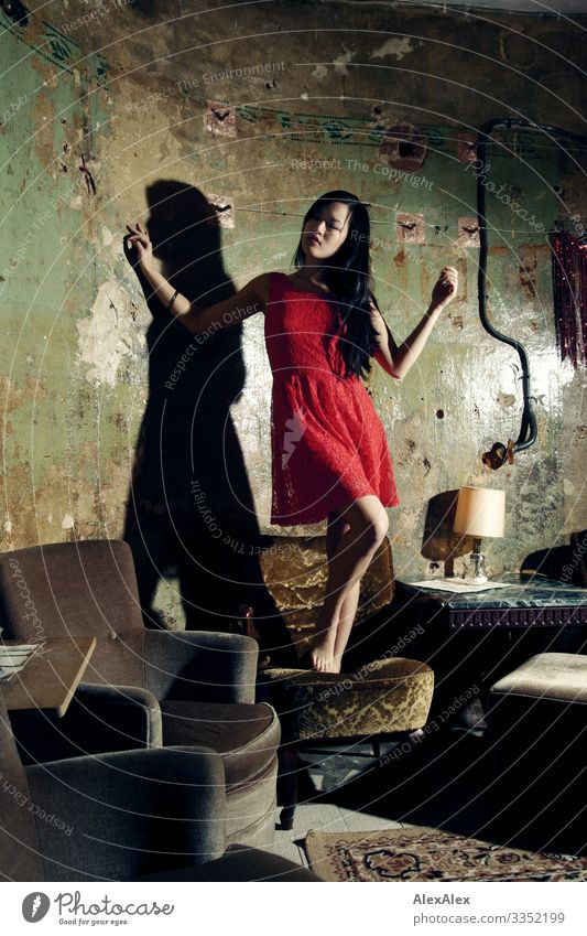Portrait of a young woman in red dress on an armchair Style Joy Beautiful Life Armchair Living room Young woman Youth (Young adults) 18 - 30 years Adults Dress