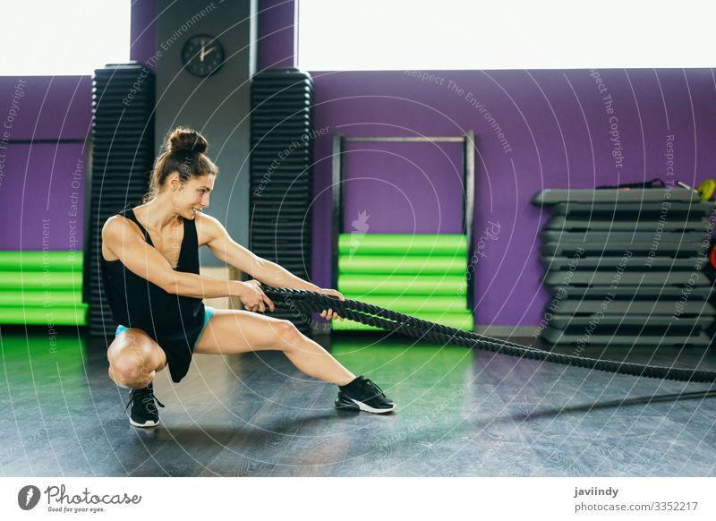 Young and athletic woman using training ropes in a gym. Lifestyle Personal hygiene Body Wellness Club Disco Sports Rope Human being Feminine Young woman