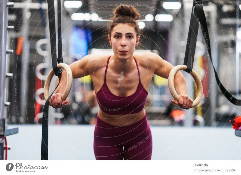 Athletic woman doing pull up exercises in the gymnastic rings Lifestyle Beautiful Body Club Disco Sports Human being Feminine Young woman Youth (Young adults)