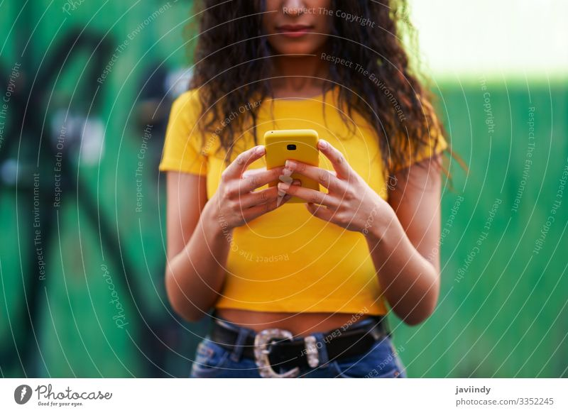 Young Arab woman walking in the street using her smartphone Lifestyle Style Happy Beautiful Hair and hairstyles Face Telephone PDA Technology Human being