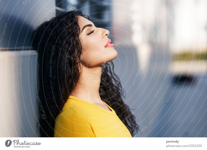 Young Arab woman with her eyes closed and her head leaning against the wall in the street. Lifestyle Style Beautiful Hair and hairstyles Make-up Sun Human being