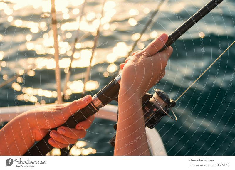 Female hands hold a fishing rod for fishing. Lifestyle Relaxation Leisure and hobbies Fishing (Angle) Vacation & Travel Trip Ocean Entertainment Woman Adults