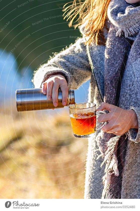A young girl pours herbal tea into a glass mug. Tea Lifestyle Joy Wellness Relaxation Leisure and hobbies Sun Woman Adults Hand Autumn Wind Warmth Leaf Park