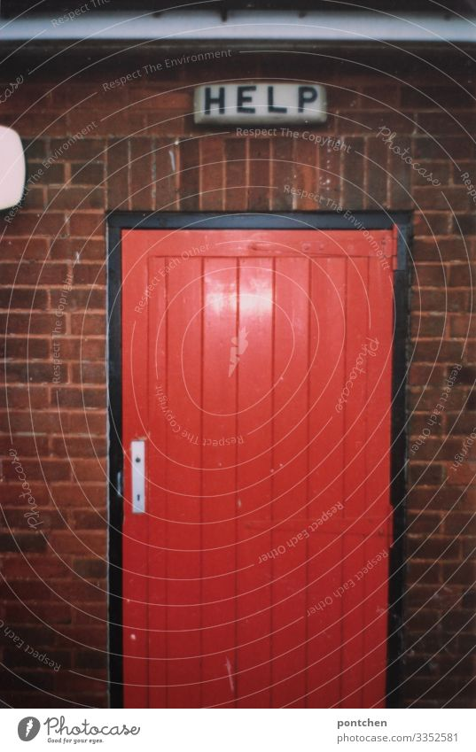 Sign with inscription Help above red door England Building Communicate Door Seeking help First Aid Brick Red Toilet Signs and labeling Mechanism Illuminate