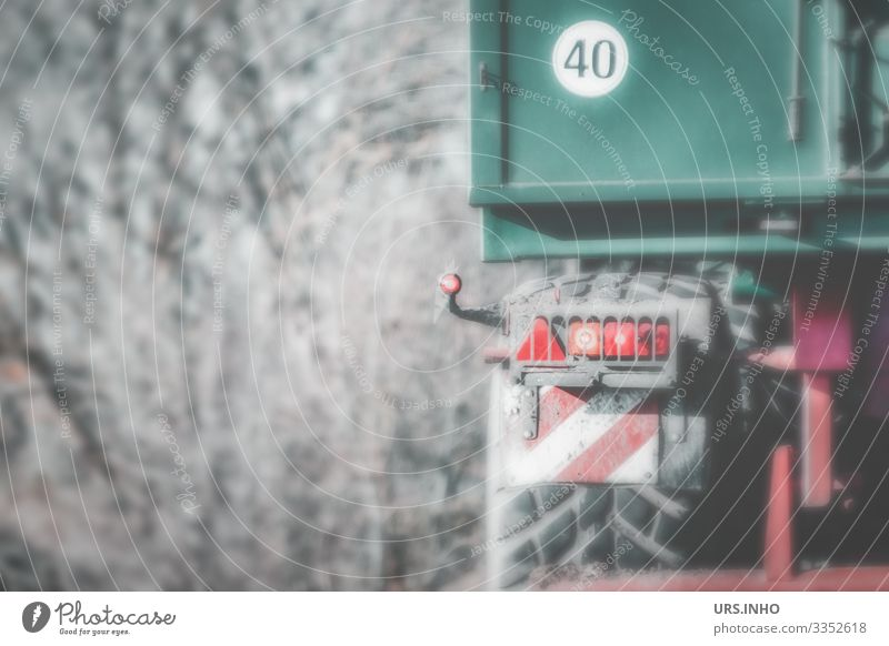 Part of a trailer with sticker 40 Logistics Truck Trailer Digits and numbers Driving Disgust Brown Gray green Red Black Tire Rear light Agriculture Colour photo