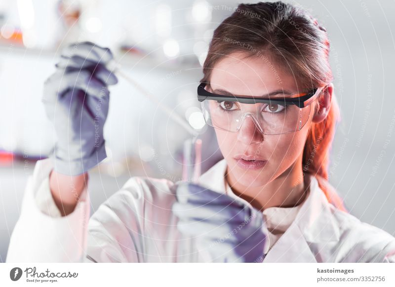 Young scientist pipetting in life science laboratory. Woman Human being Blue White Adults Environment Health care Work and employment Technology Glass Future