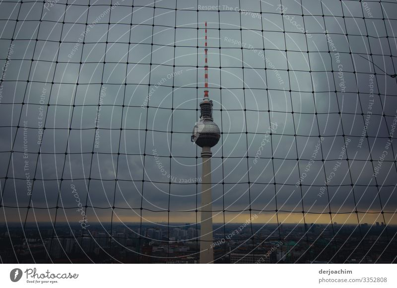 Bad weather at the Berlin TV tower tower. The tower is behind a grid. The background is dark. Design Life Telecommunications Environment Summer Downtown
