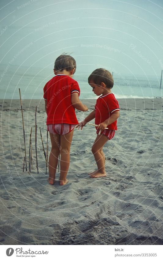 Two little girls in partner look, playing on the beach, building a fence with sticks and listening to the sea. Parenting Child Freedom Playing luck Nature