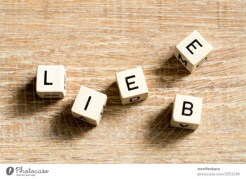 Wooden cubes with letters form the lettering LIEBE on a wooden background Joy Happy Couple Partner Life Cube Characters Love Emotions Joie de vivre (Vitality)