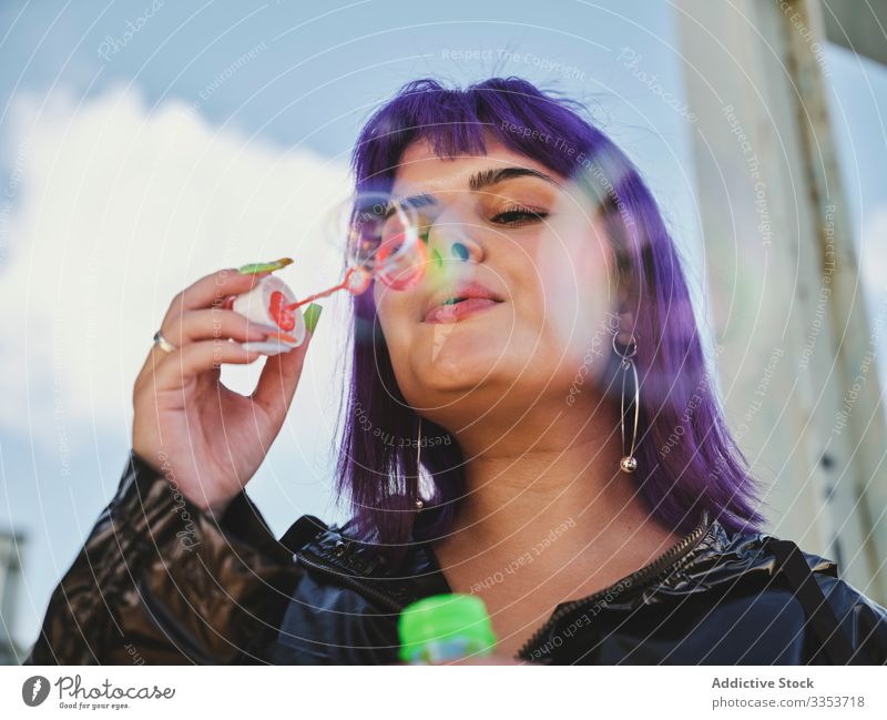 Woman blowing bubbles in bright day woman purple stylish funny cute soap cheerful laughing lovely hairstyle playing joy having fun healthy creativity playful