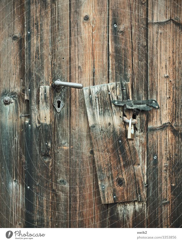 Board to Door Door handle Wooden board Metal Old Protection Safety Past Padlock Keyhole Texture of wood Wood grain Colour photo Subdued colour Exterior shot