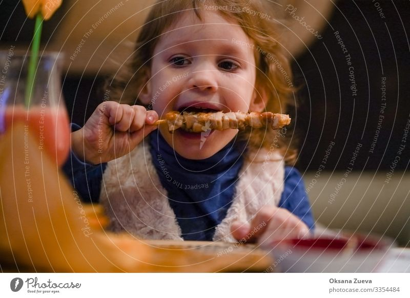 Little blonde girl eats kebab with pleasure. Dinner time. Looking into the camera Interior shot Dish meal time enjoyment Tasty Meal food little girl kid