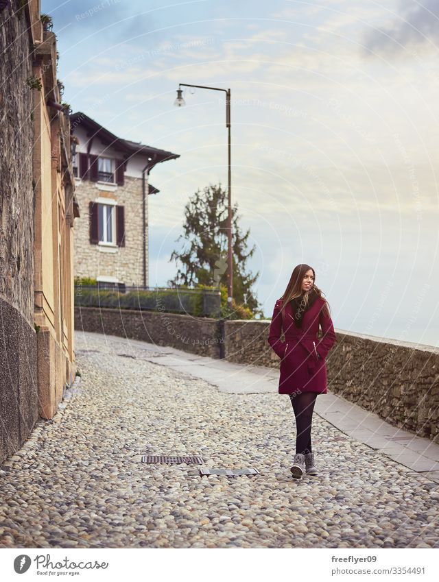 Young woman walking by a pedestrian street in italy red coat young blonde sky hiking tourism europe european trip holiday discover sightseeing vacation relaxing
