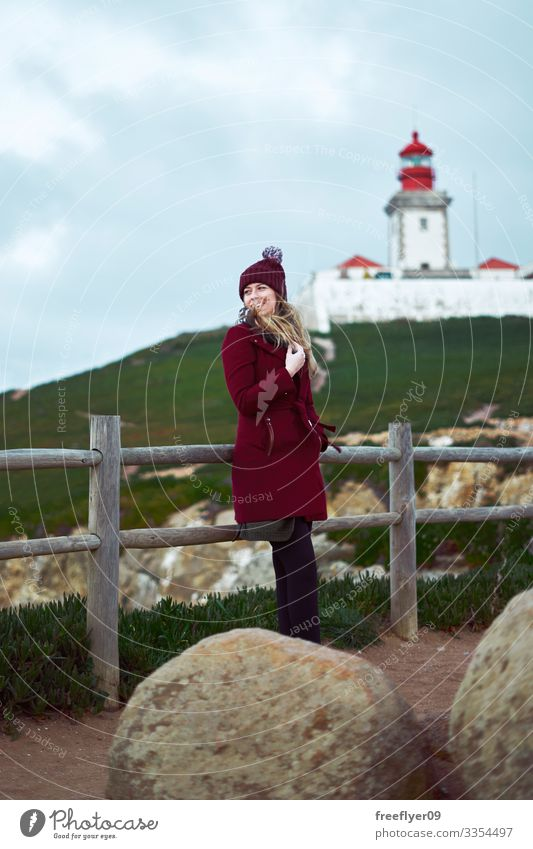 Young coman in a red coat enjoying the wind with a lighthouse on the background woman outdoor winter vertical tourist tourism hiking green grass shoreline