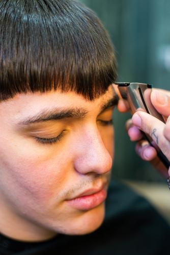 Close up of a working barber man client professional style care hairdresser design adult coiffure young beautician hand haircut comb caucasian male beauty