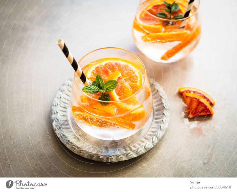 Cocktail with fresh oranges and peppermint in one glass Orange Herbs and spices Mint Diet Beverage Drinking water Lemonade Juice Longdrink Plate Glass Straw