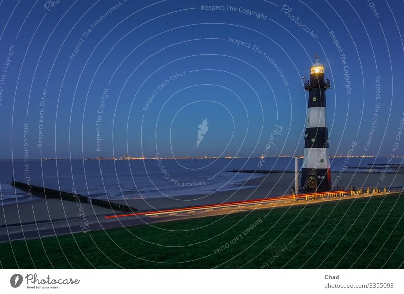 Luminous tower Beach Ocean Architecture Environment Nature Air Water Sky Cloudless sky Climate Grass Waves Coast North Sea Tower Lighthouse Manmade structures