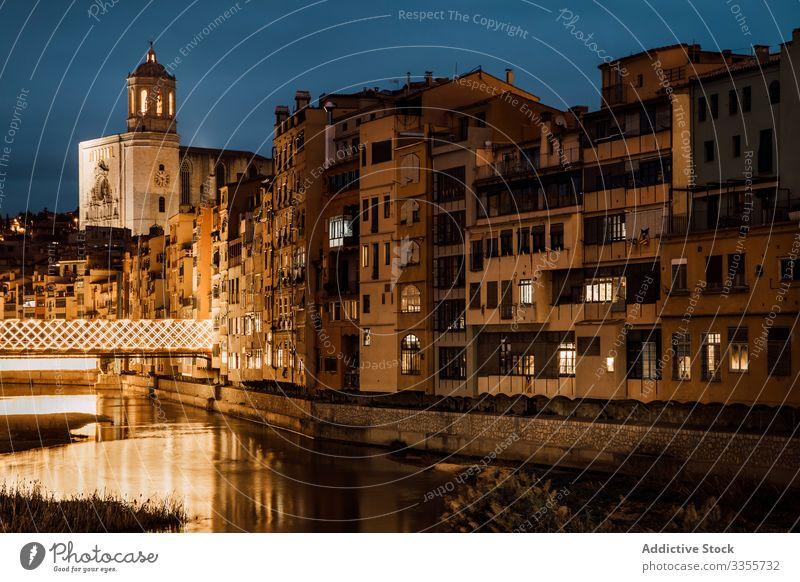 River reflecting city light flowing along buildings in evening church architecture reflection river illumination travel tourism houses girona catalonia spain