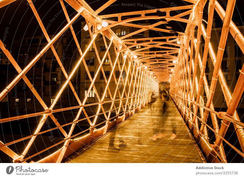 People walking on illuminated bridge construction in evening people illumination city leaning urban architecture building night twilight landmark dusk girona