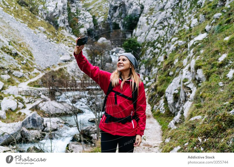 Woman with backpack taking selfie on smartphone on background of mountains woman tourist using travel nature device gadget dry peak photographing trekking