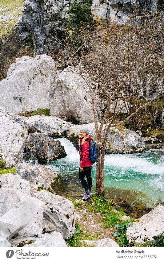 Tourist on stone and enjoying mountain waterfall and lake in mountain woman tourist watching hill travel nature peak landscape tourism adventure dangerous