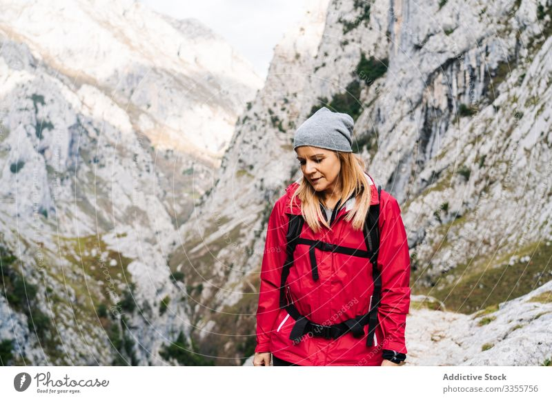 Tourist with backpack walking among high rocks woman tourist peak female mountain hill travel nature trekking landscape sky tourism adventure dangerous extreme