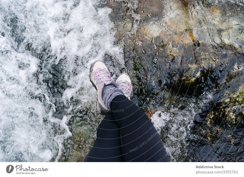 Tired tourist with backpack sitting dangling legs on bridge above mountain river village gangling legs using travel nature house peak landscape architecture