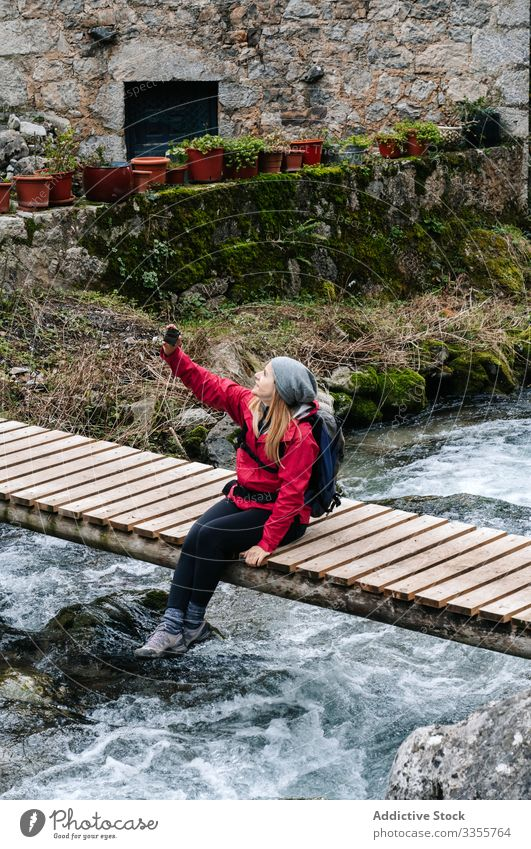 Pleased tourist with backpack taking selfie on smartphone sitting on bridge above mountain river village house using travel nature device gadget dry peak