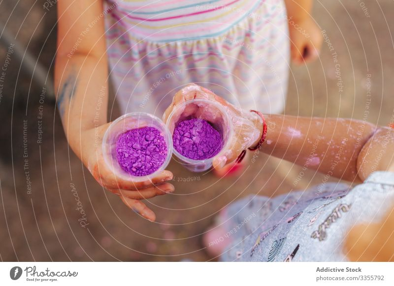 Little girls showing cups with paint in park festival summer together friend celebration little kid child season pigment dye powder demonstrate holiday