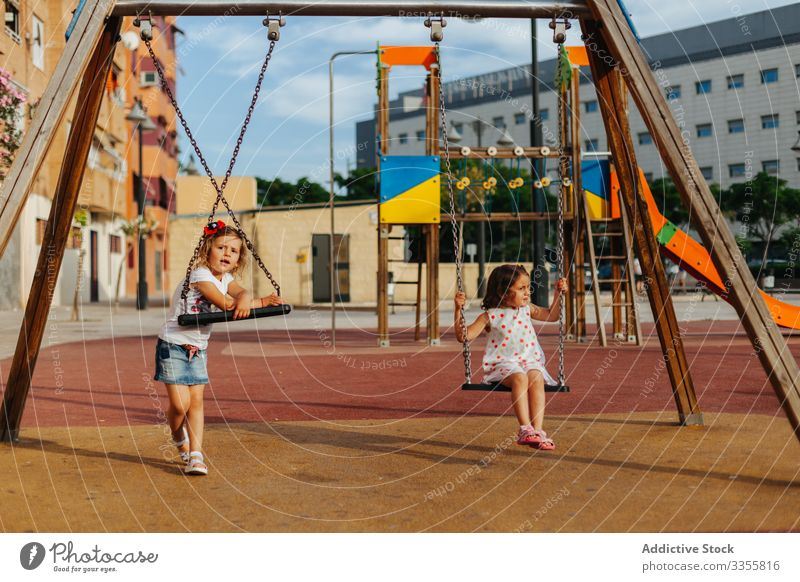 Girls on swing in park girls playground rest summer sit sunny kids weekend children childhood fun little relax lifestyle cute adorable innocence calm tranquil