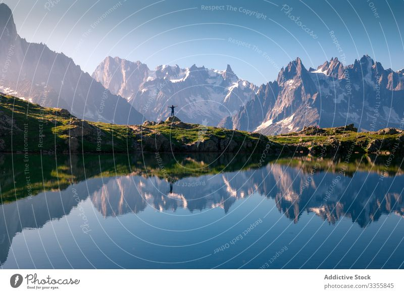Lonely tourist on hilly shore reflecting in crystal lake in snowy mountains in sunlight rock reflection clear travel landscape blue tourism natural peak sky