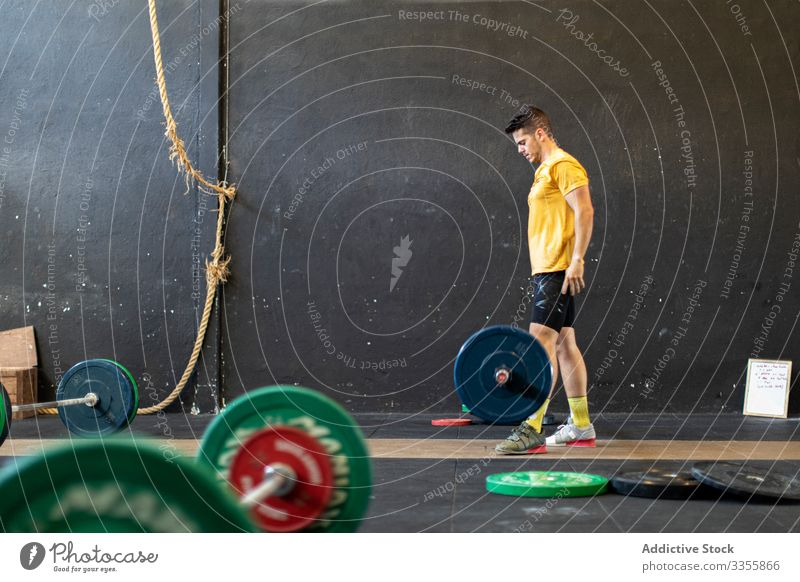 Muscular guy lifting barbell in modern gym sportsman workout weightlifting heavy effort adult strong male strained exercise athlete raised arms sportswear