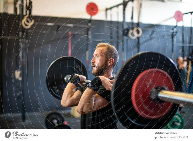 Muscular guy lifting barbell in modern gym sportsman workout weightlifting heavy effort adult strong male strained exercise athlete sportswear practice healthy