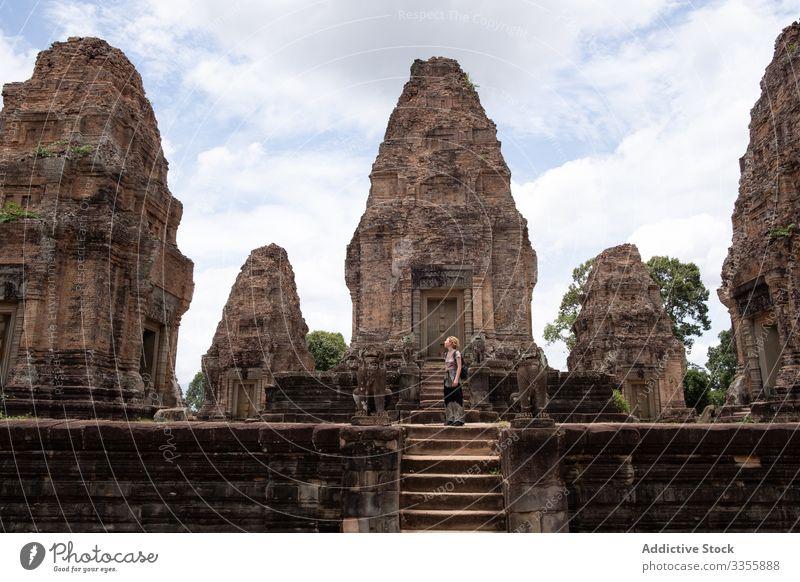 Faceless female traveler sightseeing ancient temple woman ruin religious tourist enjoy journey hindu landmark architecture tourism culture building historical