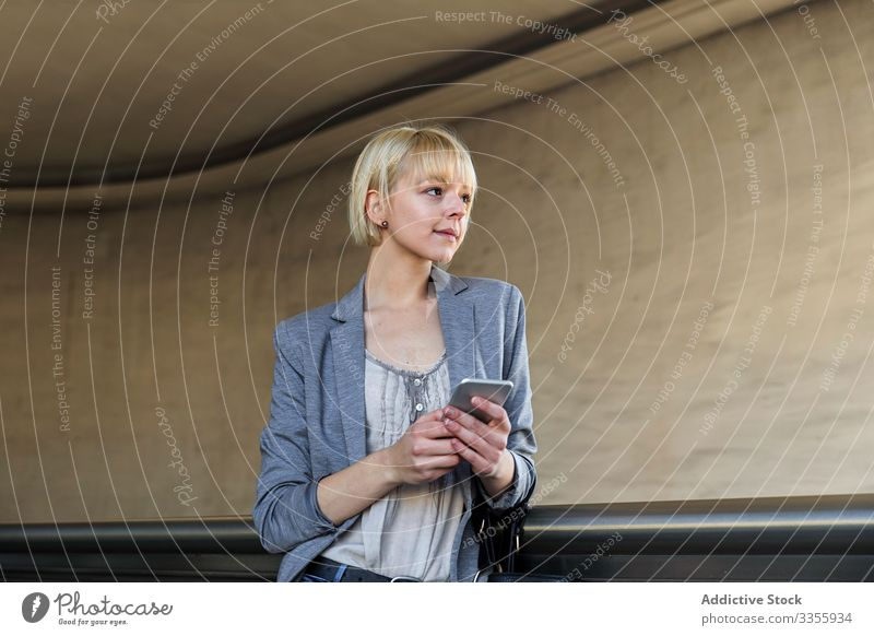Smiling businesswoman with smartphone stylish young cheerful handrail leaning female professional person beautiful smiling using browsing attractive