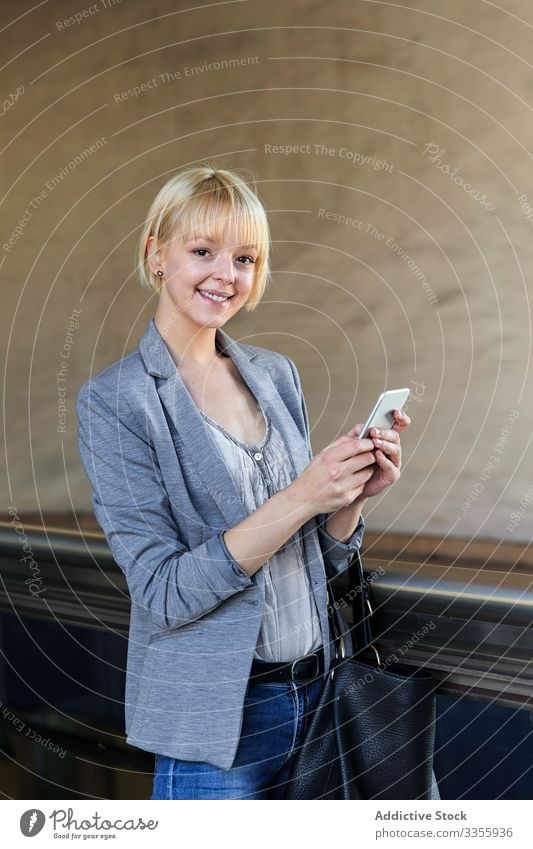 Smiling businesswoman with smartphone stylish young cheerful handrail female professional person beautiful smiling using browsing looking at camera attractive