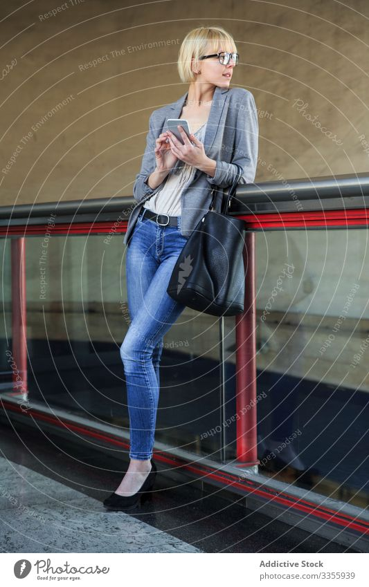 Businesswoman with smartphone businesswoman stylish young mobile connection cheerful handrail leaning female professional person beautiful using browsing