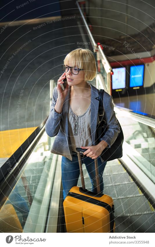 Businesswoman with luggage talking on phone businesswoman stylish young smartphone moving stairs female professional person beautiful escalator baggage trip