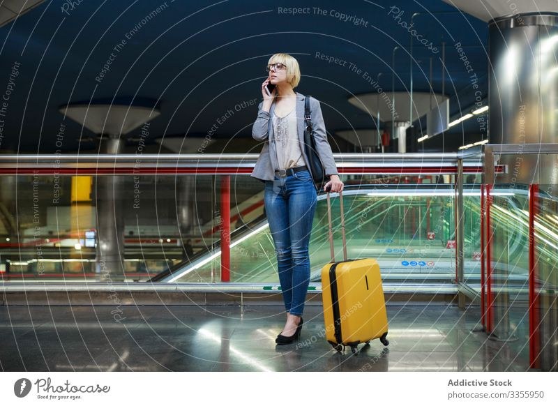 Businesswoman with luggage talking on phone businesswoman stylish young smartphone mobile connection female professional person beautiful baggage trip travel