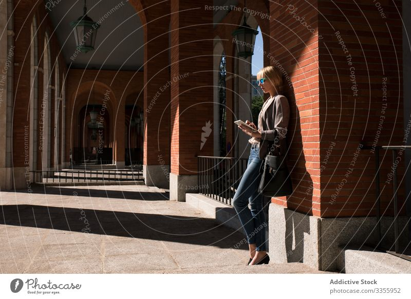 Businesswoman with tablet at wall businesswoman stylish young browsing watching leaning brick wall female professional person beautiful attractive sunglasses