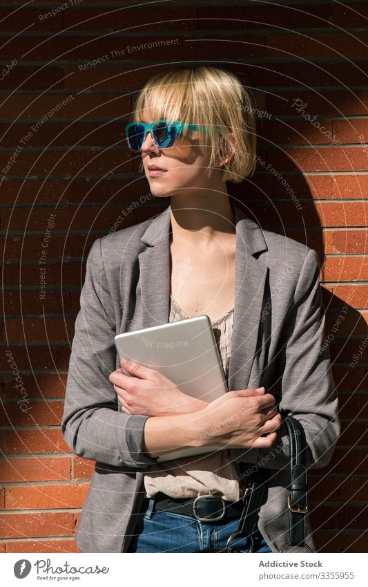 Businesswoman with tablet at wall businesswoman stylish young leaning brick wall female professional person beautiful attractive sunglasses looking away